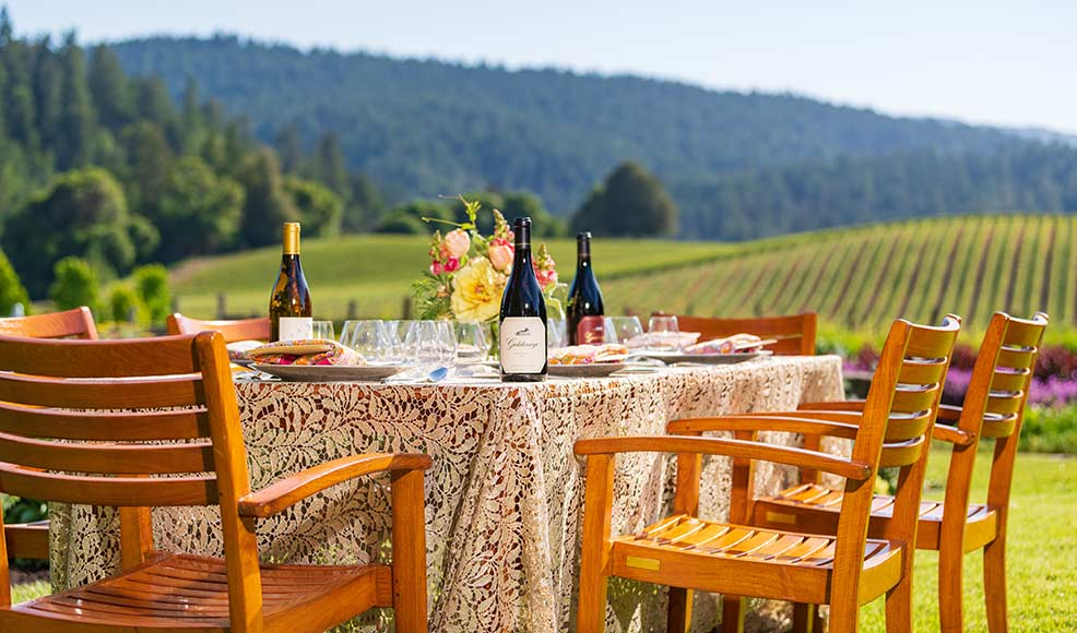 Bottles of Goldeneye and Migration wines on a table overlooking a vineyard